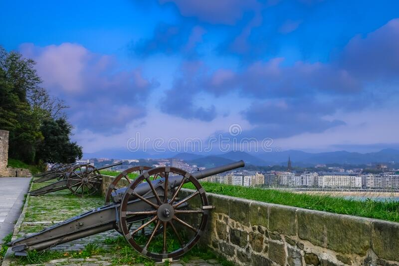 Cannons Mota Castle and a beautiful sunset view from the fortress of the city of Donostia San Sebastian in the Bay of Biscay,. Basque Country, Spain stock images