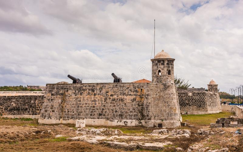Cannons and Towers - Morro Castle. Havana, Cuba / March 22, 2016: Cannons atop wall and lookout towers at Morro Castle where it historically guards Havana Bay stock image