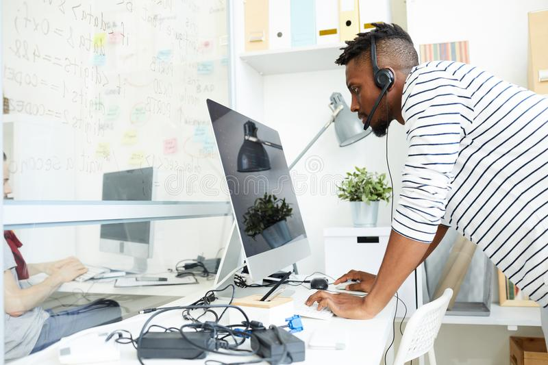 Cannot quit work. Serious guy in headset concentrating on reading online data on computer screen and talking to clients stock image