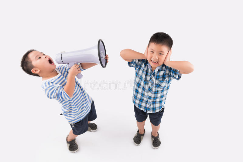 Cannot stand this noise. Little boy cowering ears when his brother shouting into megaphone stock photography