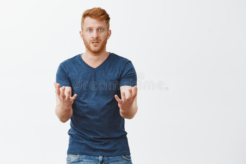 Cannot understand how it happened. Portrait of confused upset ginger man in despair with bristle, lifting hands in stock photo