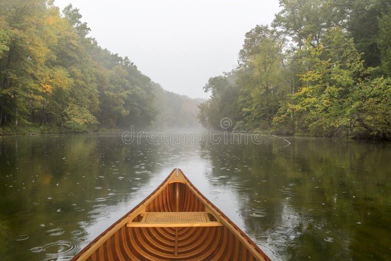 Canoë de cèdre sur une rivière pendant une pluie légère photographie stock libre de droits