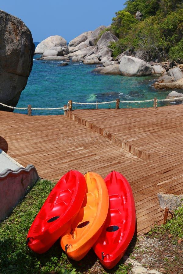 Canoë rouge à la mer dans le costume bleu lumineux de tourisme de la Thaïlande grand images libres de droits