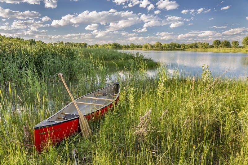 Canoë rouge sur le rivage de lac photographie stock