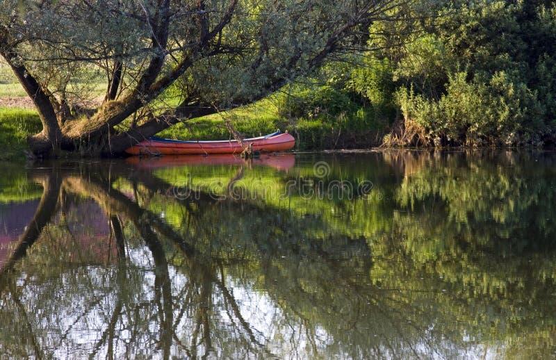 Canoë rouge sur le Riverbank photos stock