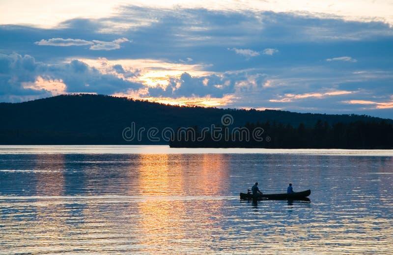 Canoë sur le lac au coucher du soleil photographie stock libre de droits