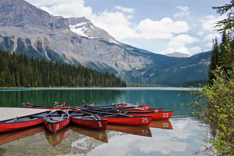 Canoës rouges sur un lac vert image stock