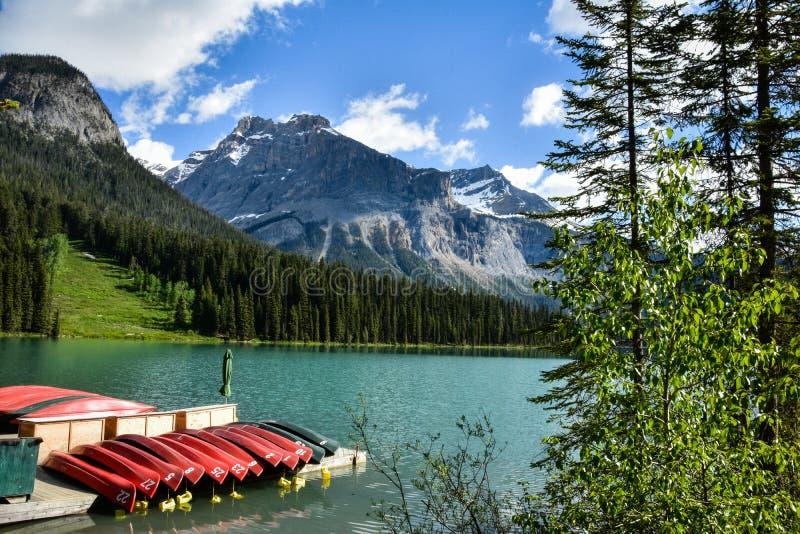 Canoës sur un dock au beau lac vert photos libres de droits