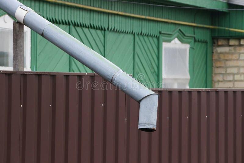 Cano cinzento longo do metal na parede marrom da cerca imagens de stock