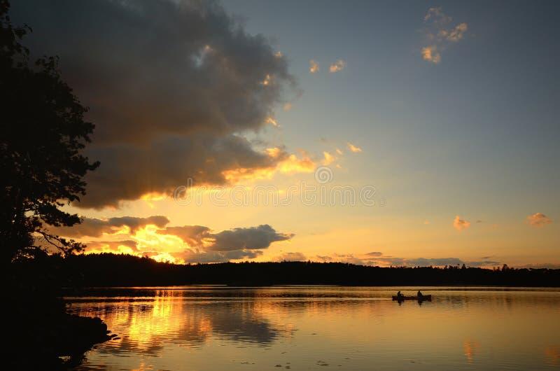 Canoa al tramonto su un lago wilderness immagine stock libera da diritti