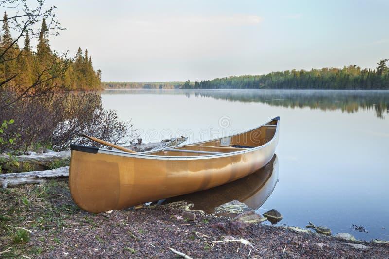 Canoa amarela na costa do lago do norte Minnesota na luz do amanhecer imagens de stock