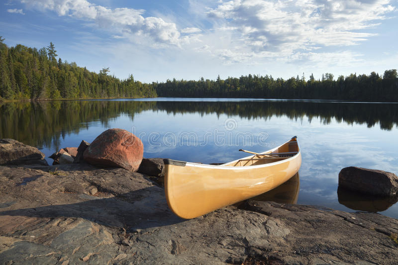 Canoa amarela na costa rochosa do lago calmo com pinheiros fotos de stock