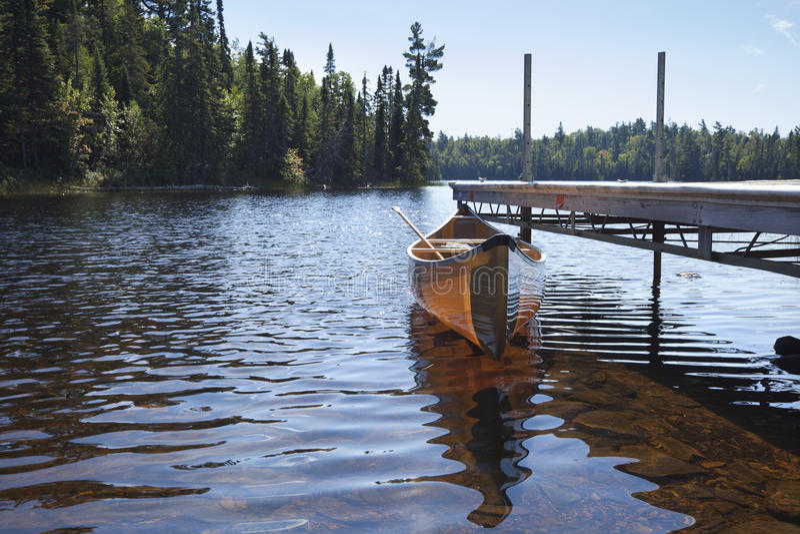 Canoa amarrada a uma doca em um lago em Minnesota do norte fotografia de stock royalty free