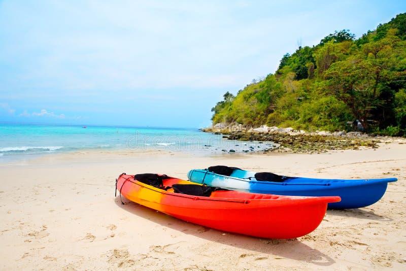 Canoa colorida dos en la playa arenosa imagenes de archivo