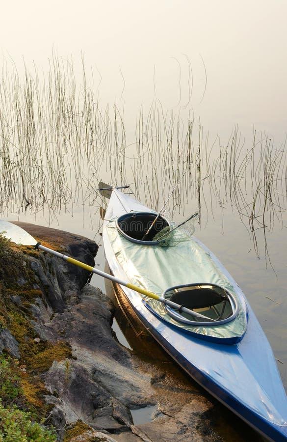 Canoa com remo e pesca-equipamento na região selvagem foto de stock royalty free