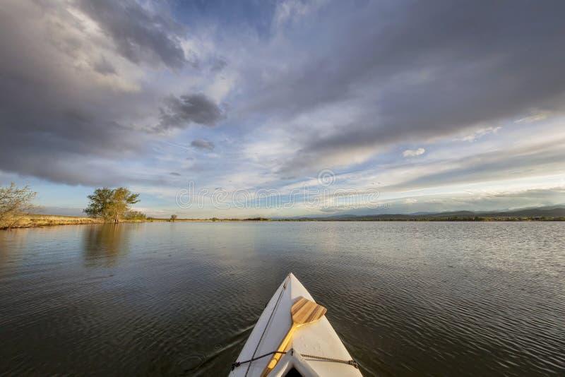Canoa con una pagaia sul lago fotografie stock