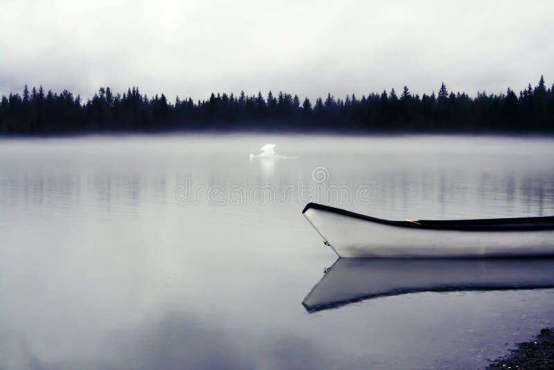 Canoa de Alaska solitaria en un lago de niebla imagenes de archivo
