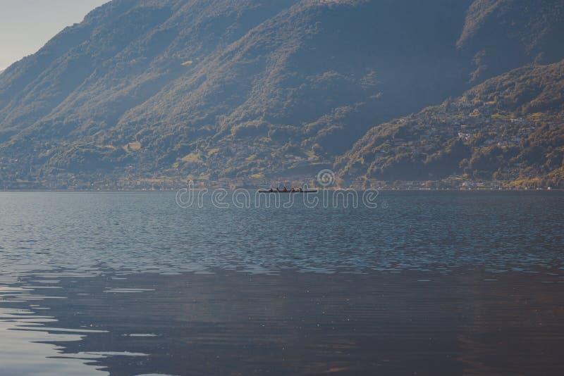 Canoa de cuatro hombres en el lago fotos de archivo