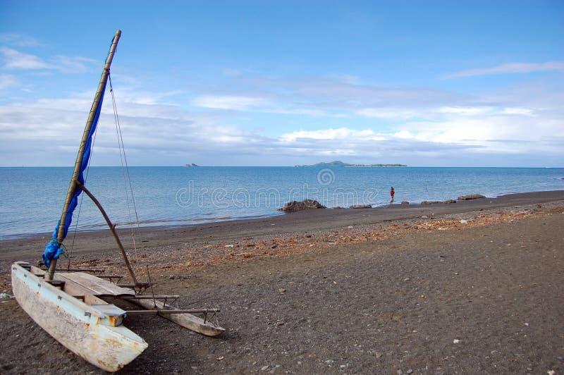 Canoa de la navegación en la playa del océano fotos de archivo