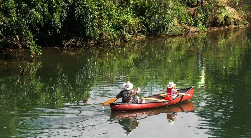 Canoa della figlia e del padre sul fiume fotografia stock