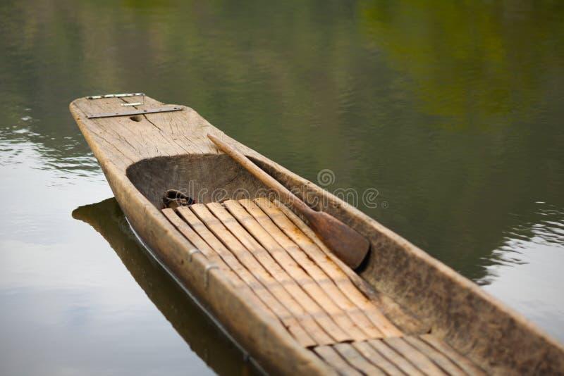 Canoa di legno con un remo sull'acqua calma del lago immagine stock