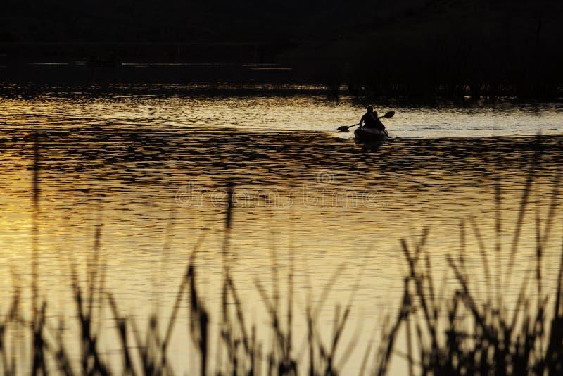 Canoa en la puesta del sol imagen de archivo