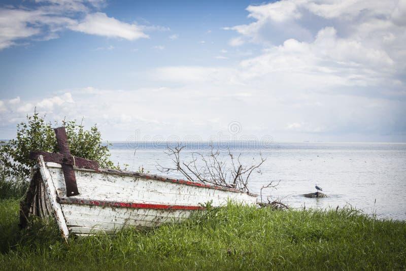 Canoa quebrada velha com uma âncora oxidada que senta-se ao lado de um lago fotos de stock royalty free