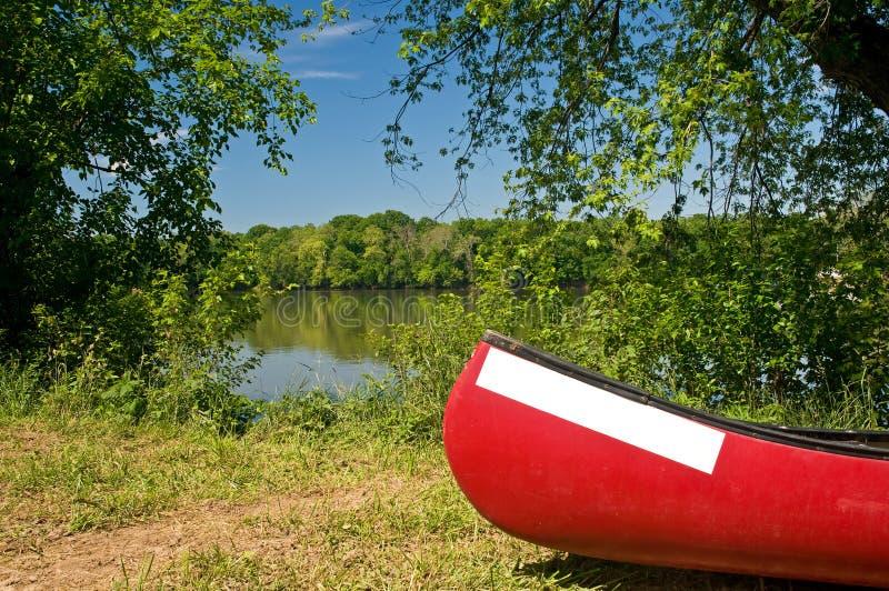 Canoa rossa sul riverbank fotografia stock