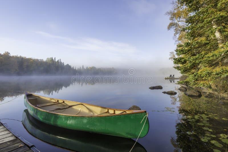 Canoa verde atada al muelle imagen de archivo