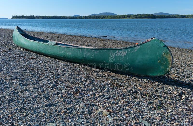 Canoa verde vieja en orilla foto de archivo libre de regalías
