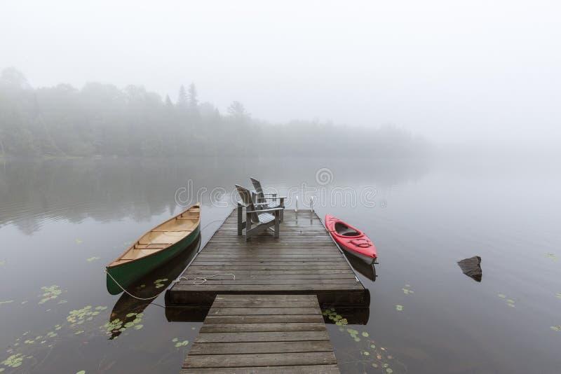 Canoa y kajak atados a un muelle en un lago Ontario brumoso, Canadá imágenes de archivo libres de regalías