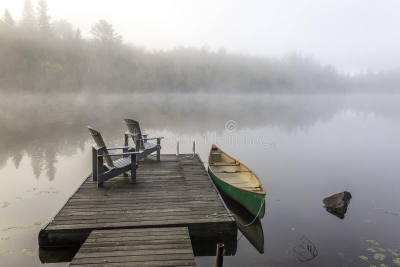 Canoa y muelle verdes en Misty Morning fotos de archivo