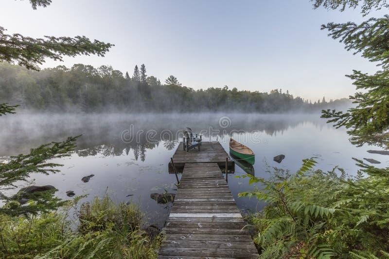 Canoa y muelle verdes en una mañana brumosa - Ontario, Canadá foto de archivo