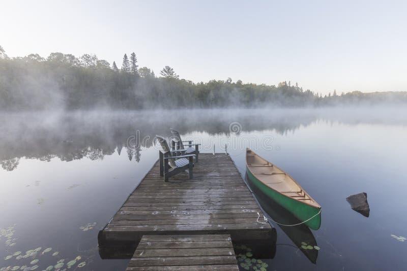 Canoa y muelle verdes en una mañana brumosa - Ontario, Canadá foto de archivo libre de regalías
