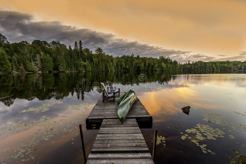 Canoa y sillas verdes en un muelle en la puesta del sol foto de archivo libre de regalías