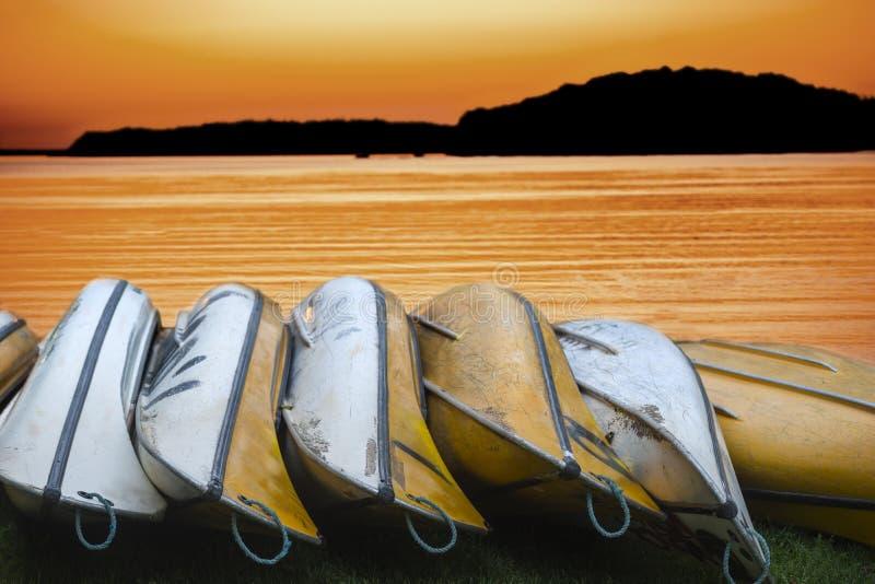 Canoas canadienses en la puesta del sol imagen de archivo