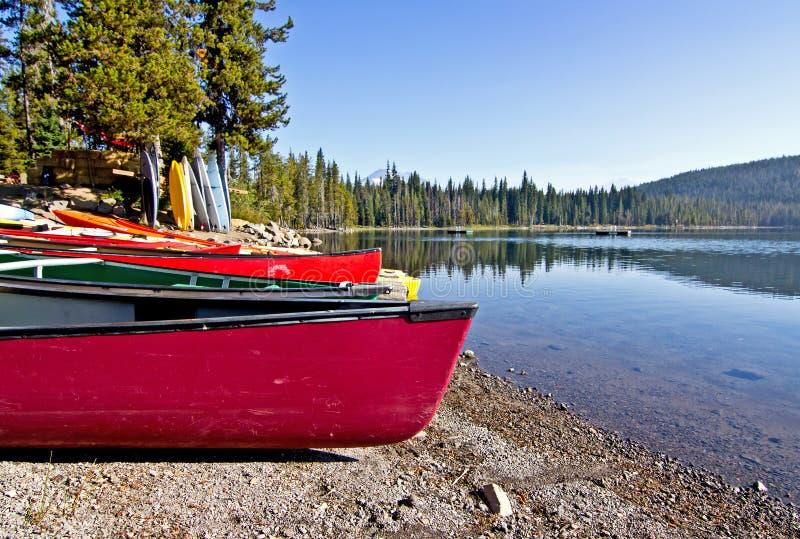 Canoas coloridas na costa do lago foto de stock