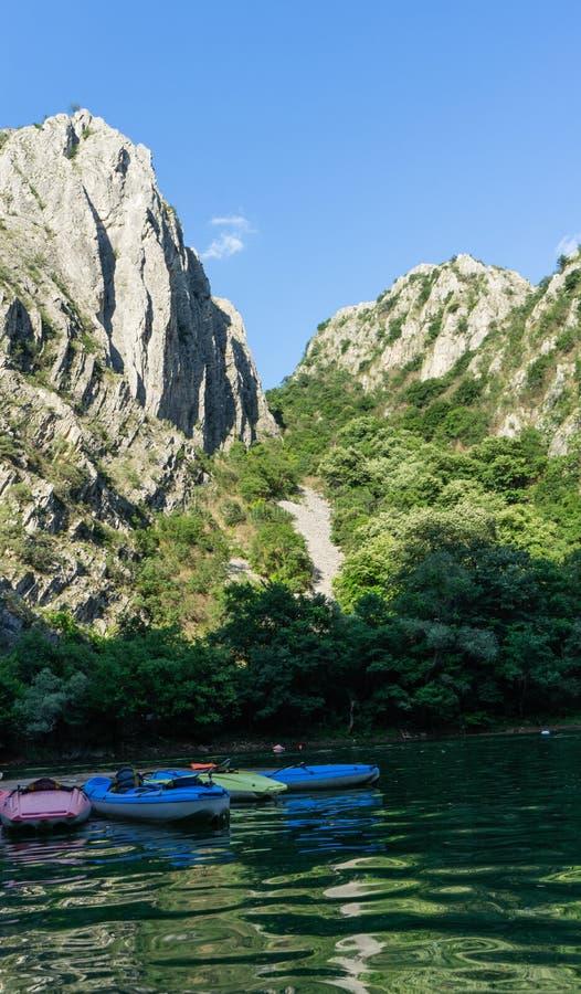 Canoas coloridas na garganta de Matka, Macedônia sem a pessoa Caiaque em um cais e em um por do sol nas montanhas e no lago fotografia de stock