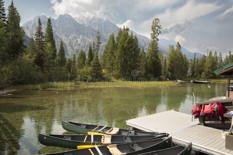 Canoas, doca e montanhas em Jenny Lake, Jackson Hole, Wyoming foto de stock