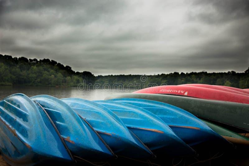 Canoas en la playa en el lago tempestuoso imagenes de archivo