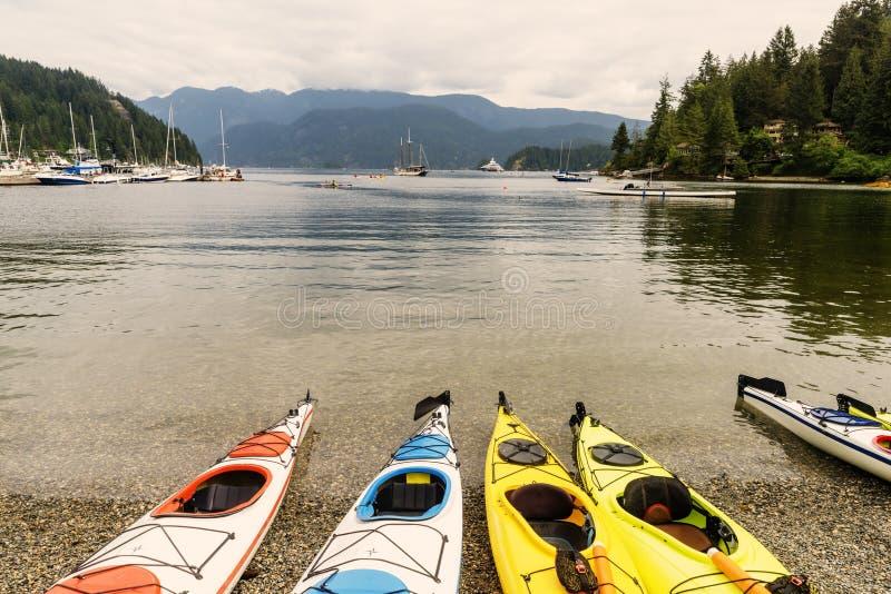 Canoas nos seixos perto da água, dos navios e dos iate claros dentro imagens de stock royalty free