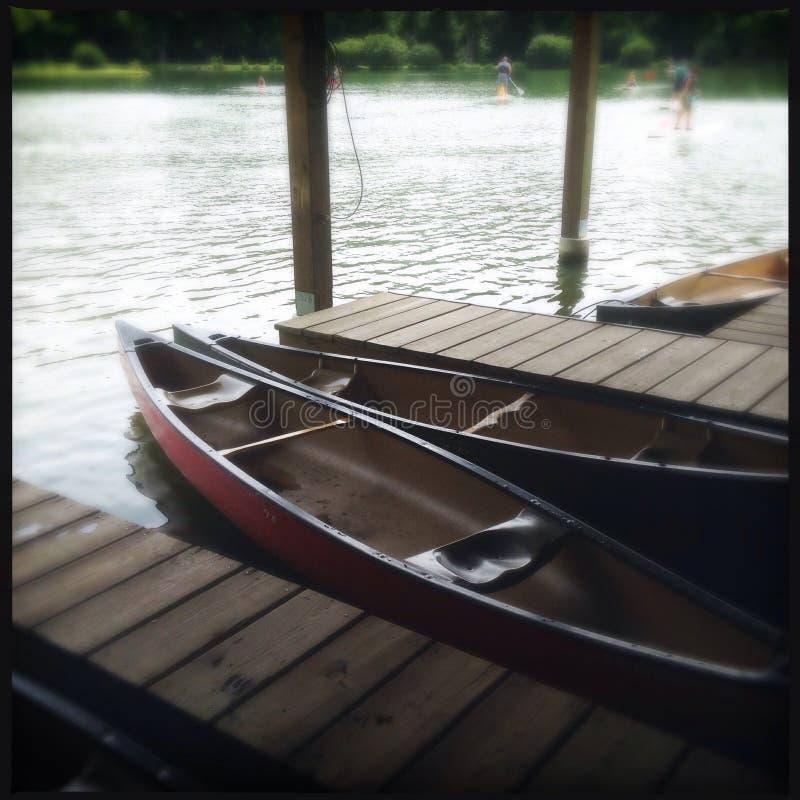 Canoas pelo lado de um lago imagem de stock