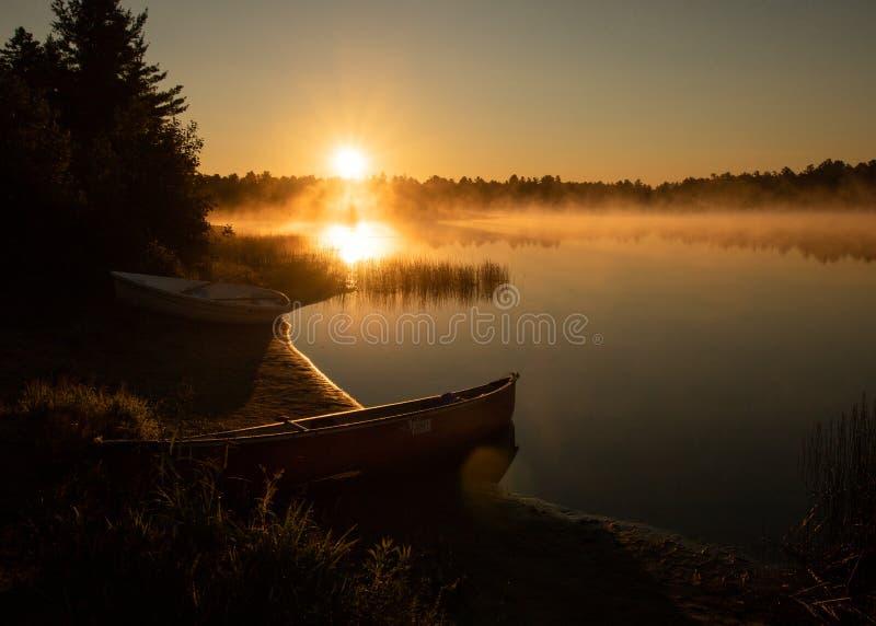 Canoe на береге туманного озера на восходе солнца/заходе солнца стоковое изображение