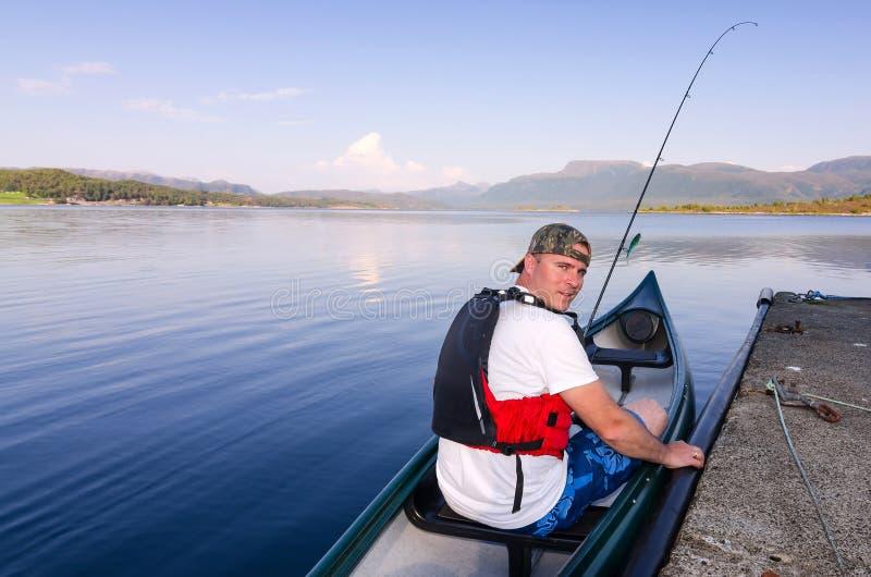 Canoe angler in Norwegian fjord stock image