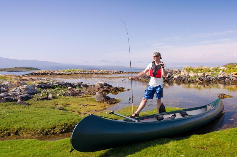 Canoe angler in Norwegian fjord scenery royalty free stock image