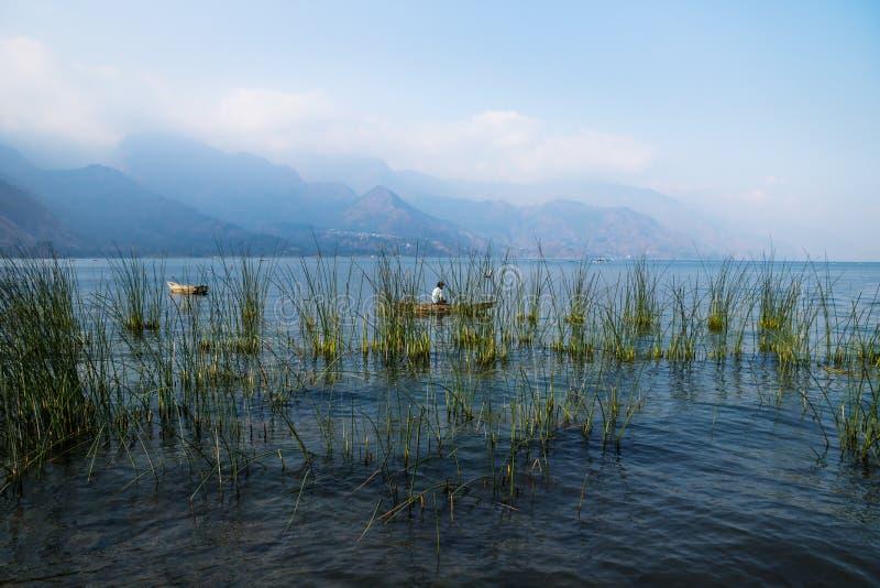 Canoe con il pescatore dietro la canna con le montagne nebbiose a Lago Atitlan, San Juan la Laguna, Guatemala, America Centrale fotografia stock libera da diritti
