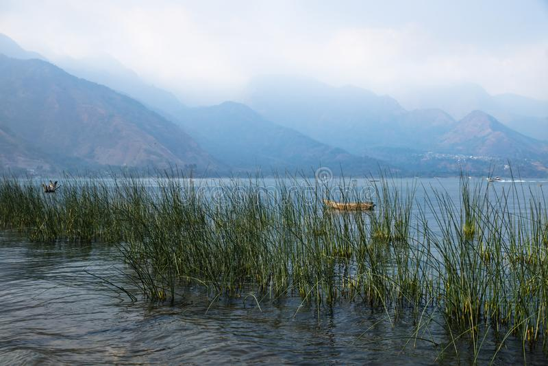 Canoe dietro la canna con le montagne nebbiose a Lago Atitlan, San Juan la Laguna, Guatemala, America Centrale fotografia stock libera da diritti