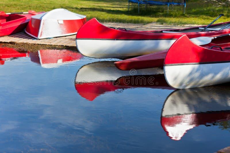 Canoe e barche rosse e bianche immagine stock