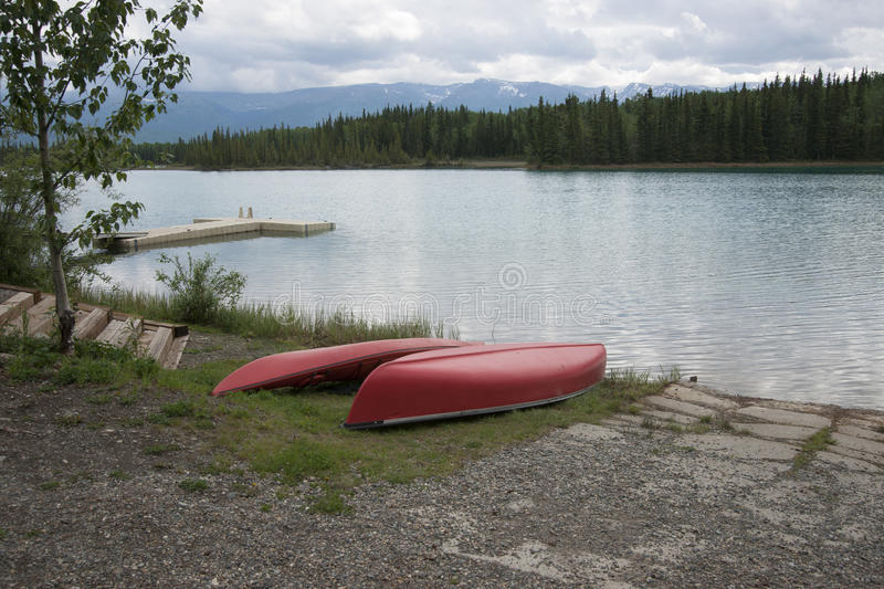 Canoe Kayak Lake Boat Launch. A red Canoe and Kayak on beach Lake Boat Launch with dock at Boya Lake on the Cassiar Highway in Northern British Columbia, Canada stock photography