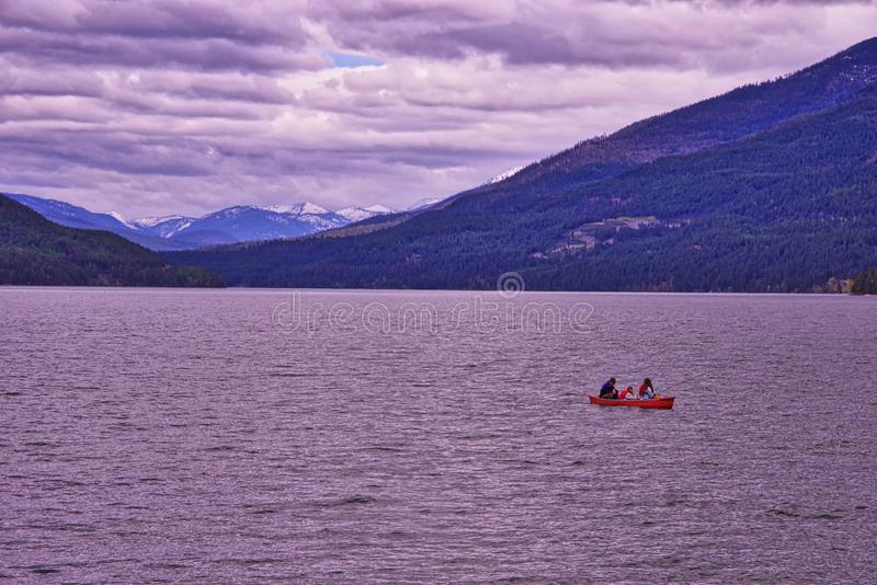 Canoeing on Whitefish Lake. Canoe on the lake Whitefish in Montana with the rocky mountains on the distance royalty free stock image
